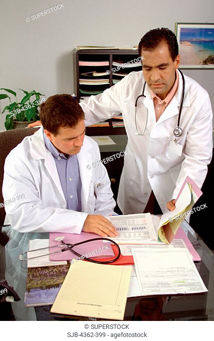 Two Doctors in Office Reviewing Patient Records