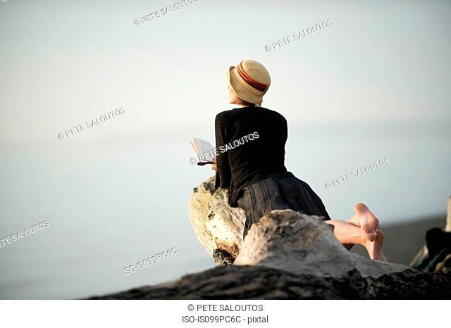 Woman lying on driftwood, looking out to sea