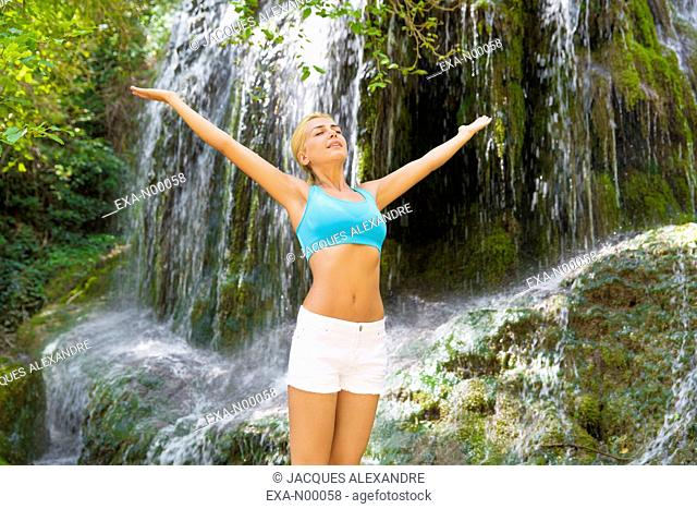 Young woman exercising with waterfall in background, streching arms, Monasterio de Piedra; Zaragoza; Aragon; Spain;