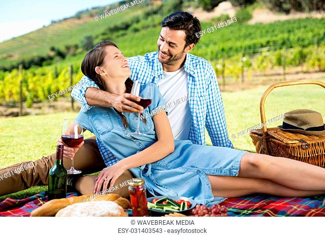 Happy couple looking at each other while holding wineglasses