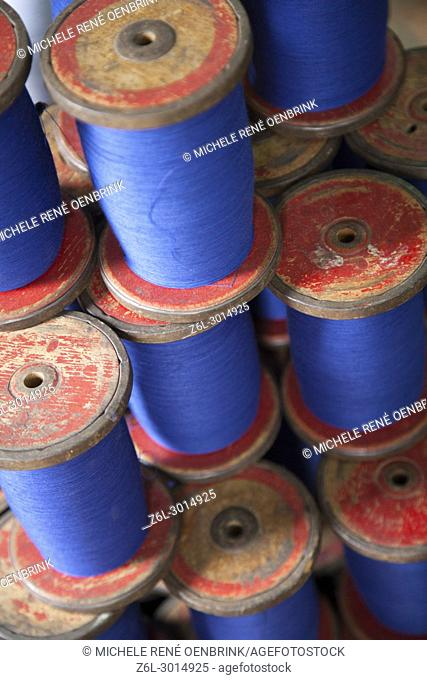 making cotton threads on spools in fabric factory in Mandalay Myanmar