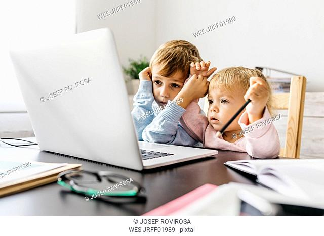 Brother and sister watching a video on a laptop