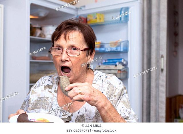 Senior woman going to eat pork liver sausage while standing in front of the open fridge in the kitchen