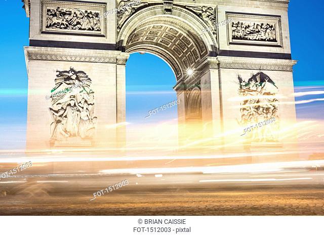 Illuminated light trails against Arc de Triomphe
