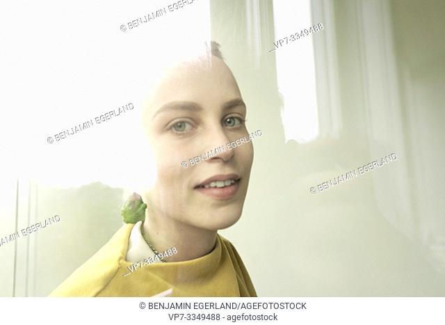young woman wearing earring made of raw zucchini