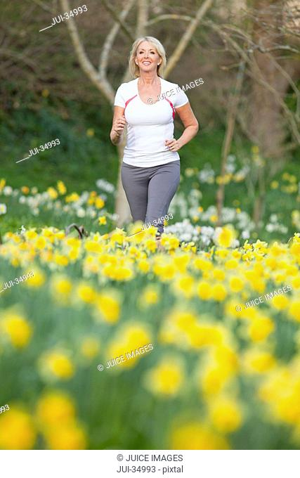 Smiling woman jogging in sunny daffodil field