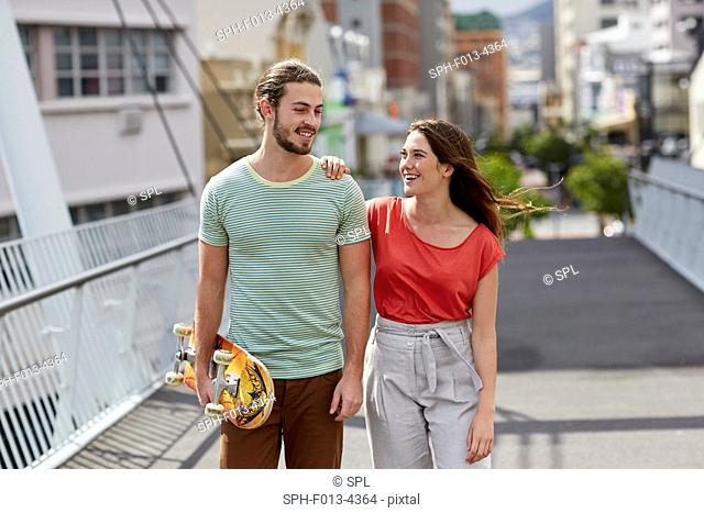 MODEL RELEASED. Young couple walking, man carrying skateboard