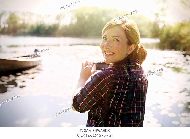 Portrait smiling woman with red hair photographing sunny lake with camera phone