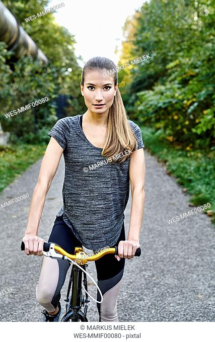 Portrait of sportive young woman with bicycle in a park