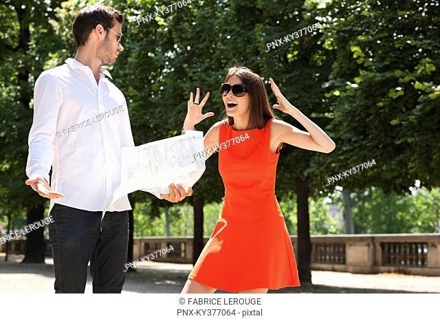 Woman shouting on a man reading a map, Terrasse De l'Orangerie, Jardin des Tuileries, Paris, Ile-de-France, France