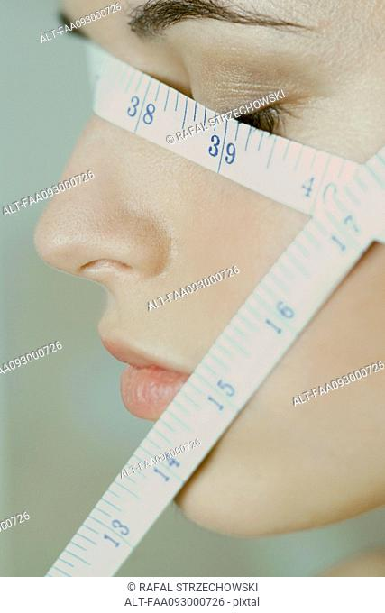 Woman with measuring tape wrapped across face, close-up