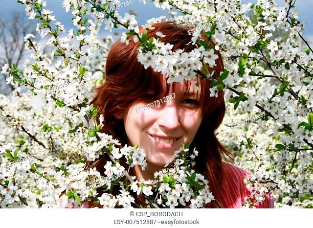 Girl in a blooming cherry tree