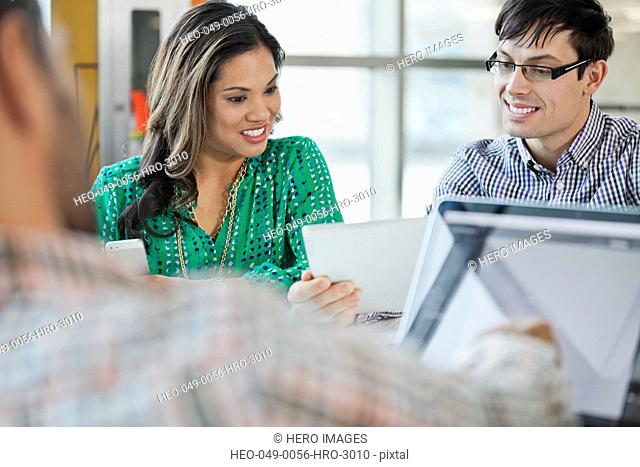 Businesspeople sharing digital tablet during meeting
