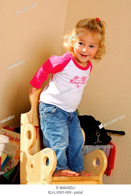 Close-up of a girl standing on a chair and smiling