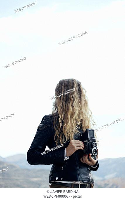 Woman with obscured face holding vintage camera