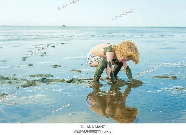 Germany, Schleswig Holstein, Boy playing in mud at beach