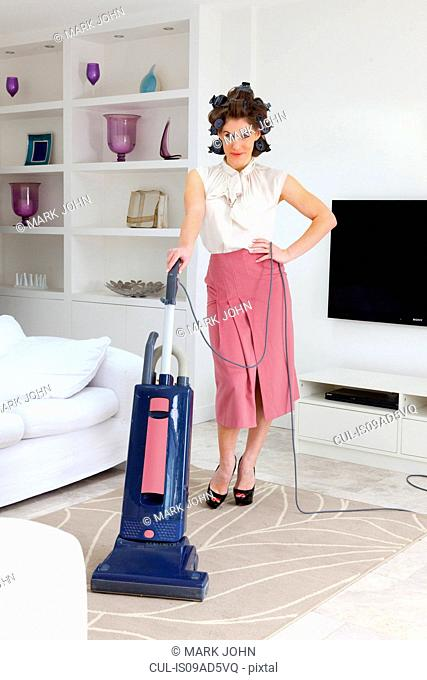 Young woman vacuuming living room