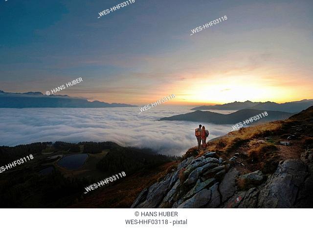Austria, Steiermark, Reiteralm, Hikers admiring view over clouds