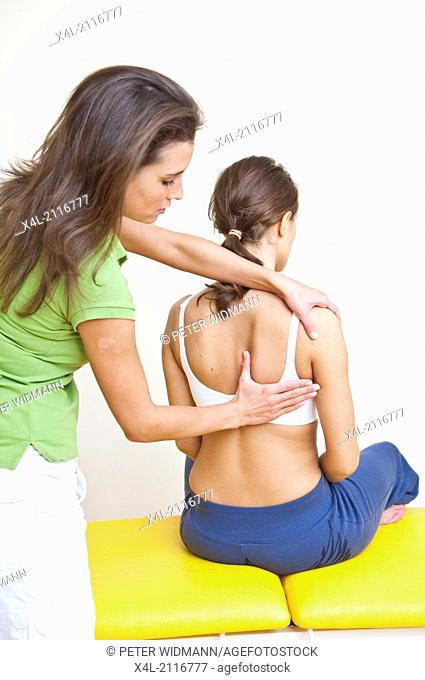therapist and patient doing spinal gymnastics (model-released)