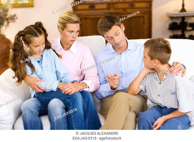 Parents talking to children on sofa
