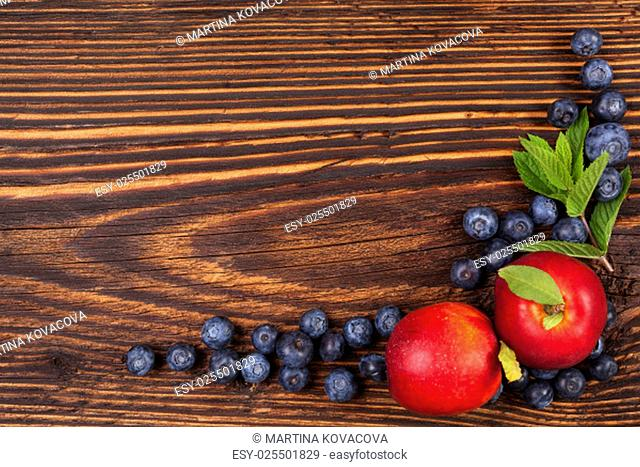 Fresh fruit background with copyspace. Blueberries and nectarines and mint leaves on wooden background, top view
