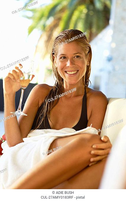 Girl relaxing on sun bed with champagne
