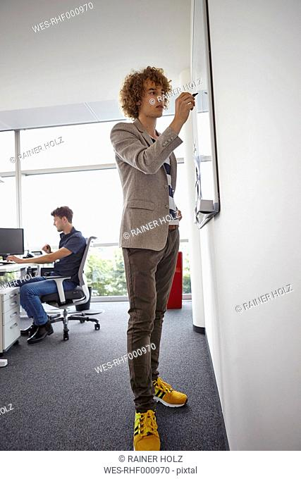 Young man in office writing on whiteboard