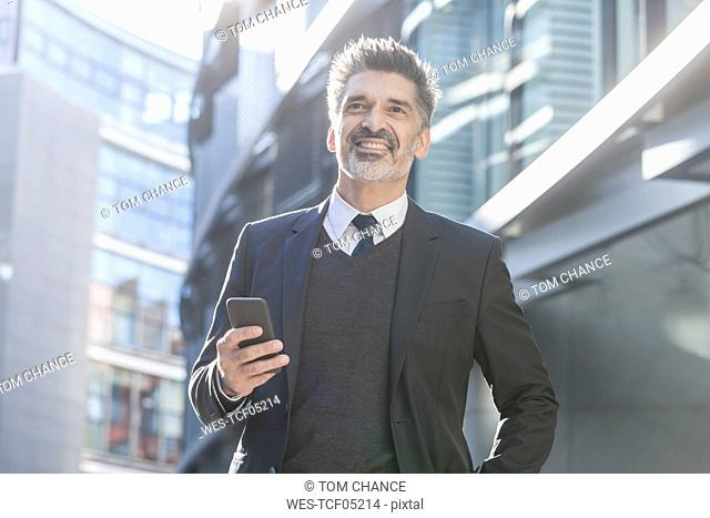 Smiling businessman outdoors with cell phone