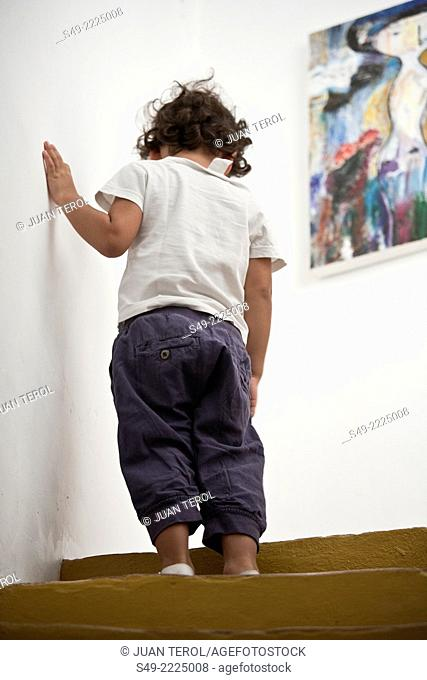 Little boy walking up steps, holding on to wall for support.