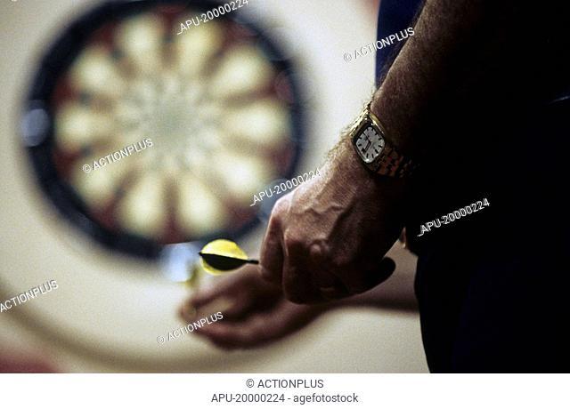 Man holding dart by dart board