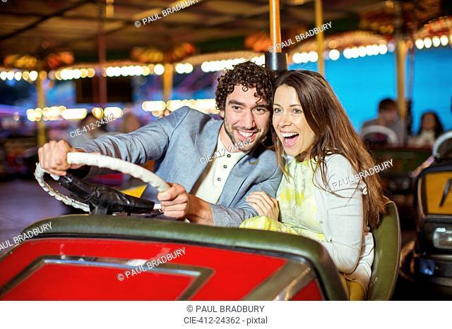 Couple on bumper car ride in amusement park