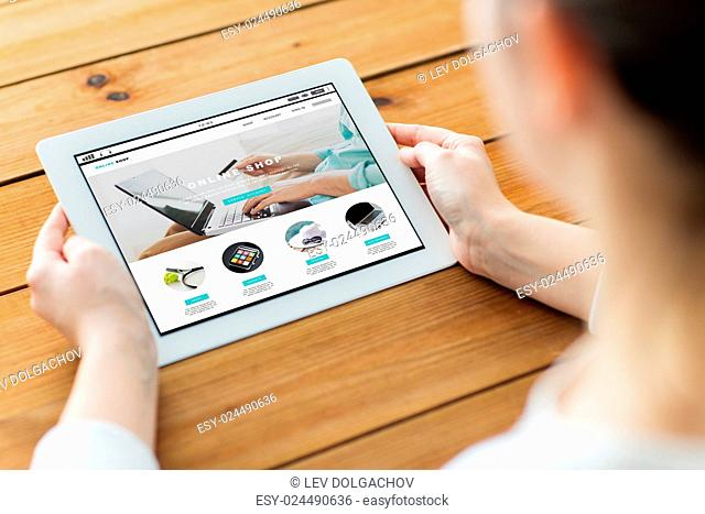 business, internet shopping, people and technology concept - close up of woman with online shop web page on tablet pc computer screen