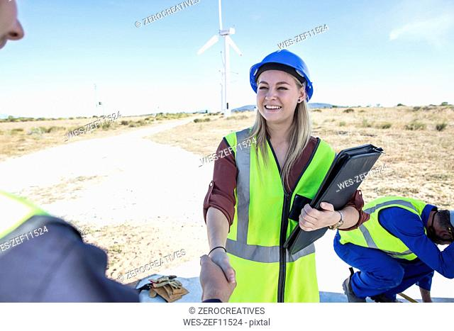 Female engineer shaking hands with colleagues on wind farm