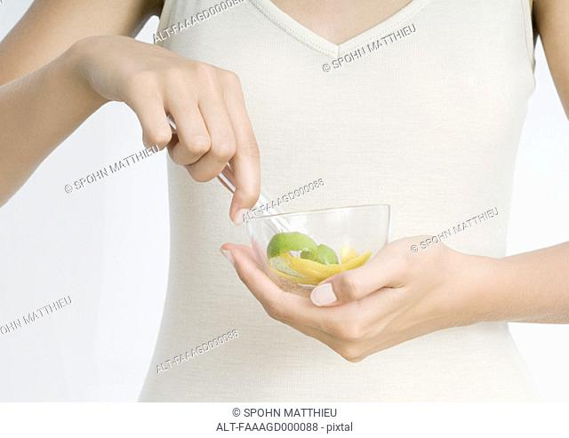 Young woman holding bowl with lemon peel and herbs
