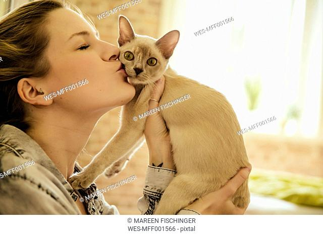 Woman kissing Burmese cat