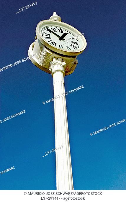 Public clock seen from below against a deep blue sky