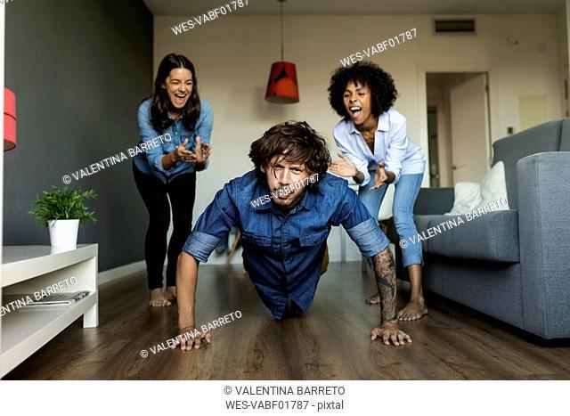 Two women encouraging man doing pushups at home