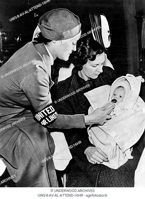 United States: c. 1947.A United Airlines stewardess gives a baby a bottle on the airplane while the mother looks on