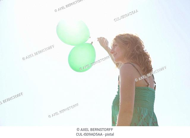 Woman holding two green balloons, Wales, UK