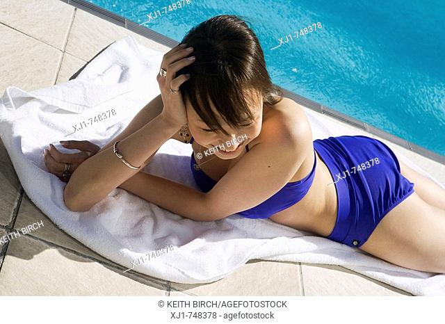 A young Japanese woman lying on a towell beside a hotel complex swimming pool