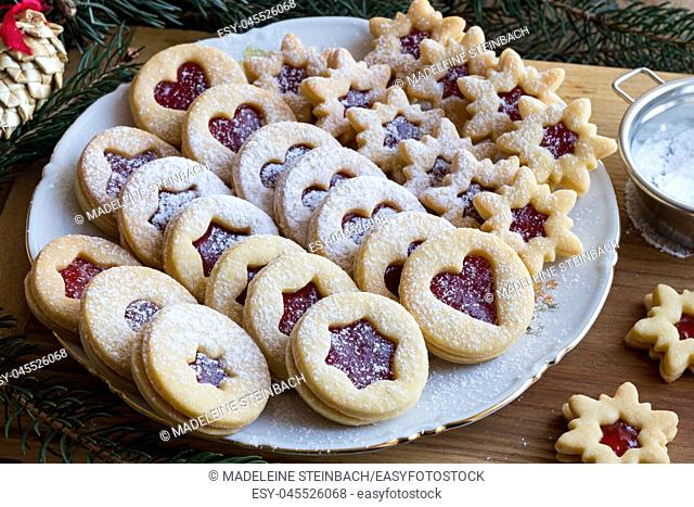 Linzer Christmas cookies filled with strawberry jam and dusted with sugar, arranged on a plate on a wooden table