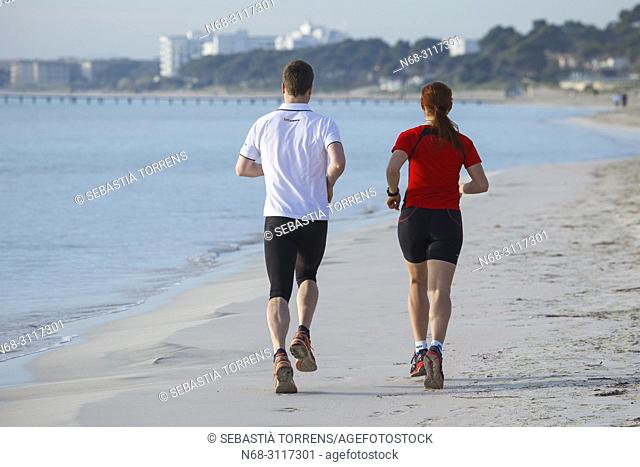 Couple running on the beach of Alcudia, Majorca, Balearic Islands, Spain