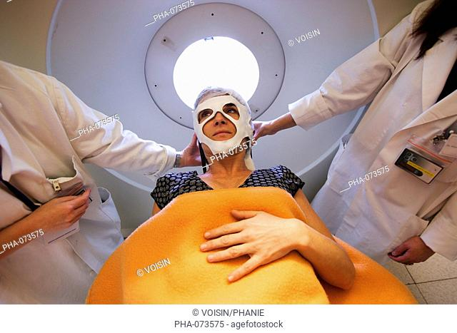 Patient undergoing Positrons Emission Tomography scan PET scan of the brain. A nurse applies a thermoformed mask on the face of the patient to prevent from...