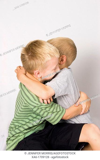 A pair of young blond haired boys, brothers, embrace against a pale background