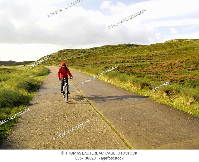 A woman with her bicycle on an old street, Sylt, Germany