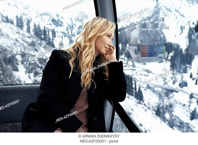 Switzerland, European Alps, Woman looking out at the mountain range from the cable car gondola