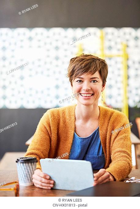 Portrait smiling businesswoman using digital tablet drinking coffee at cafe table