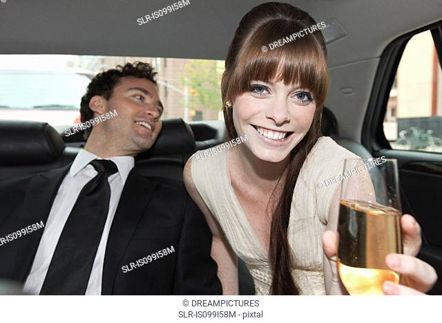 Newlywed couple in car with champagne