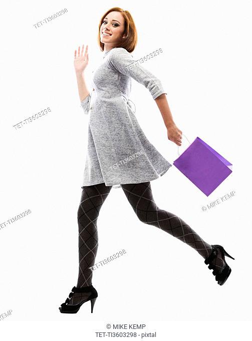 Young woman running with shopping bag, studio shot
