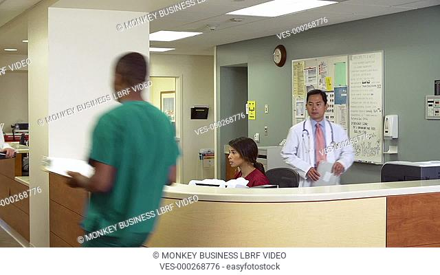 Medical staff working around busy medical reception desk.Shot on Sony FS700 in PAL format at a frame rate of 25fps